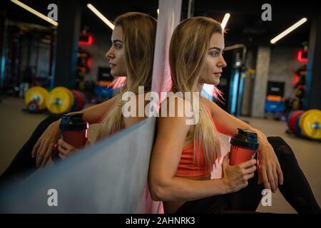 Young Pretty Woman descansando después de hacer ejercicio en el gimnasio