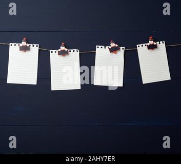 Cuaderno de hojas de papel blanco vacío colgando sobre vacaciones decorativos clothespins, azul de fondo de madera. Limpiar la hoja, la plantilla. Elemento de diseño.