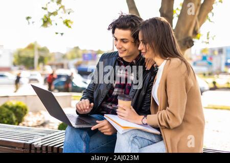Feliz pareja joven con ordenador portátil sentado en un banco en la ciudad exterior - Concepto de relación y personas adictas a la tecnología retrato