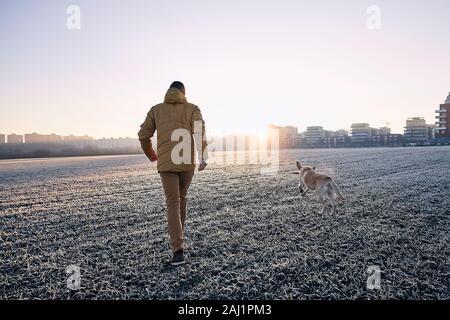 La helada mañana con el perro. Joven caminando con su perro contra el paisaje urbano al amanecer. Foto de stock
