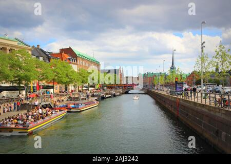 Barcos de excursión en un canal y Slotsholmen Gammel Strand calle bordeada por una hilera de coloridas casas antiguas en el centro de la ciudad de Copenhague, Dinamarca