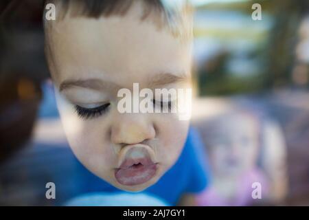El niño empuja sus labios hacia arriba contra una ventana para hacer un beso