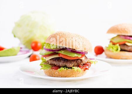 Sándwich grande - Hamburger hamburguesa con carne, aguacate, tomate y cebolla roja sobre fondo claro. Cocina americana. La comida rápida Foto de stock