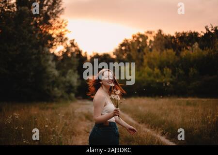 Mujer joven mirando hacia atrás mientras corre en el campo en el bosque en verano