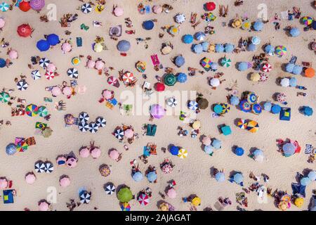 Río de Janeiro, Brasil, vista superior de la playa de Copacabana mostrando coloridas sombrillas y gente relajándose en un día de verano.