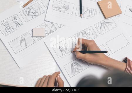 La mano de la mujer dibuja un guión gráfico para una película o una caricatura.