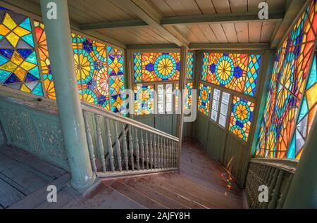 Tbilisi, Georgia: Interior de famosos y tradicionales de madera antigua casa georgiana con coloridos vitrales y escalera de madera Foto de stock