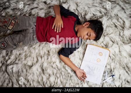 El colegial durmiendo mientras haciendo los deberes en casa