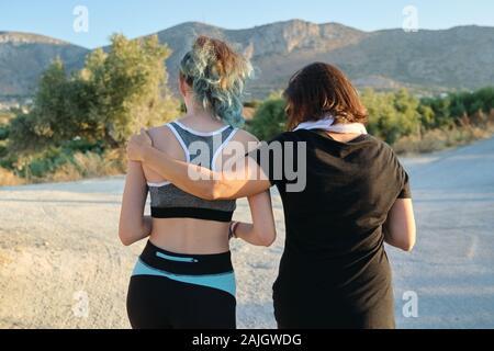 Activo y Saludable de la familia atlética, madre e hija adolescente caminando en ropa deportiva