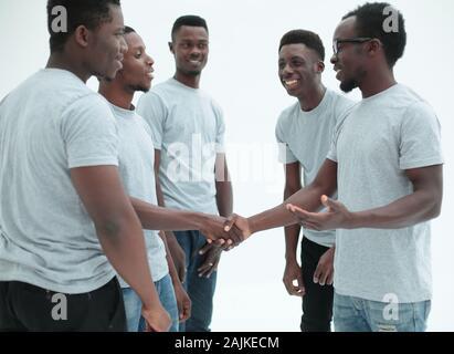 Los jóvenes un apretón de manos, de pie en un círculo de amigos