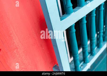 Callejón colorido con ventanas de madera en pared roja con sombras