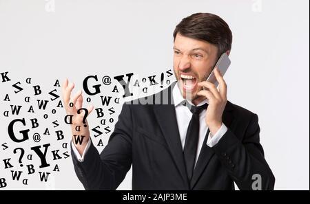 Furia de teléfono. Empresario furiosa gritando mientras hablan por celular, diversas las letras del alfabeto que sale de su boca, luz de fondo Studio