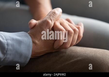 Vista de cerca de pareja de ancianos tomados de la mano