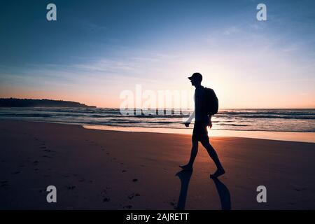 Joven con mochila caminar sobre la arena de la playa tropical. La costa de Sri Lanka en bellos amaneceres.