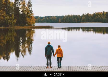 Pareja en las manos del amor romántico estilo de vida familiar que data relación hombre y mujer de pie en el muelle exterior disfrutando de lago y las tierras forestales de otoño