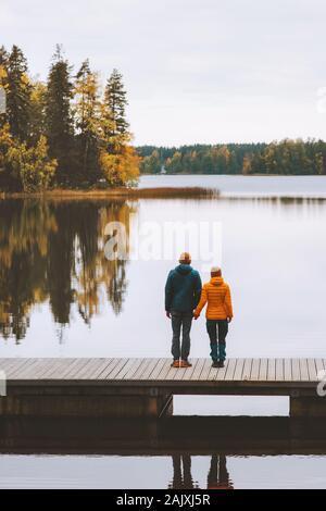 Pareja de amor viajar en Finlandia la vida familiar relación romántica el hombre y la mujer tomados de la mano de pie en el embarcadero del lago y el bosque landsc exterior