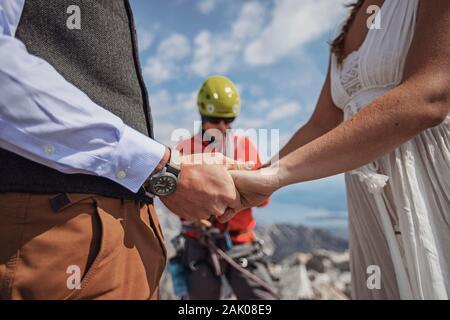 cerca de la pareja que sostiene las manos mientras se casan en una montaña