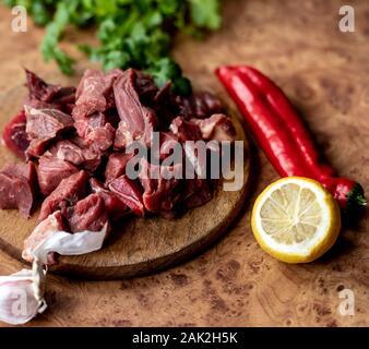 La carne de vacuno para el goulash. Carne roja cruda sobre la plancha de madera. El limón, el pimiento rojo y el ajo.