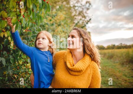 Una mujer feliz sostiene a su hija para explorar bayas rojas en un árbol