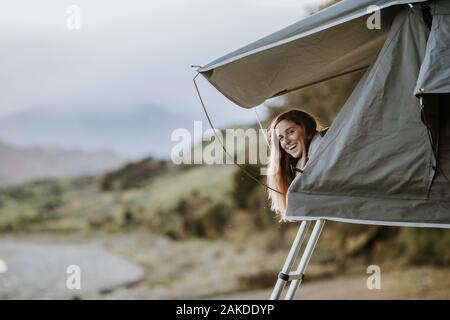 Una joven mujer sonriente se pega la cabeza de una tienda de campaña en Nueva Zelanda.