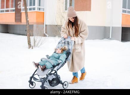 Joven madre con su hijo Baby Boy en cochecito caminando en la calle de invierno
