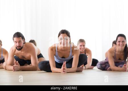 Grupo de jóvenes deportistas gente atractiva en yoga studio, practicando yoga lección con instructor, sentados en el suelo adelante franja de pose de yoga