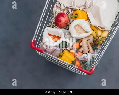 Frutas, verduras y granos en bolsas de tela reutilizables Bolsa en compras. Vista superior plana o de laicos. Cesta con alimentos producto de cerca, Foto de estudio. Los residuos alimenticios, cero residuos concepto comercial.