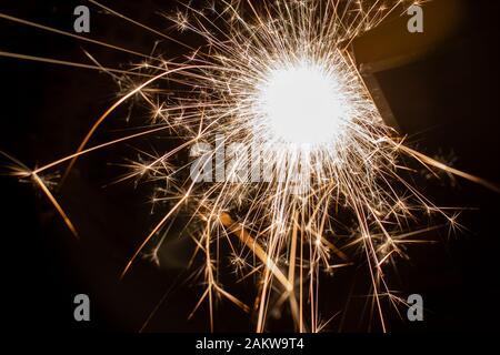 Sparkler quemando lentamente en Nochevieja. Velocidad de obturación más lenta para maximizar la luz y efectos dramáticos.