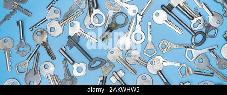 Las claves definidas sobre fondo azul. Las llaves de la cerradura de la puerta y caja fuerte de seguridad y protección de la propiedad de la casa. Diferentes antiguos y nuevos tipos de llaves.