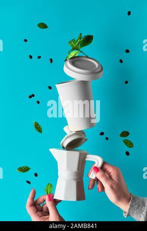 Equilibrio de cero basura pirámide de café en manos de mujeres sobre fondo de menta azul. Cafetera espresso de cerámica y taza de café reutilizable de bambú ecológica