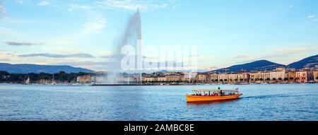 Vista panorámica del Ródano, con un barco amarillo cruzando el río el Quai Gustave-Ador en el otro lado durante la puesta de sol. Ginebra, Suiza. Foto de stock