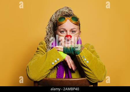 La psicóloga de la mujer madura en traje del payaso para el funcionamiento en el hospicio de los niños está en fondo amarillo. Retrato de personas reales
