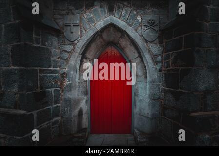 Puerta de madera roja puntiagudas de miedo en un antiguo y húmedo muro de piedra de construcción con cruz, cráneo y huesos en ambos lados. Concepto de misterio, la muerte y el peligro.