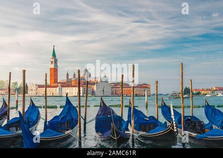 Góndolas amarradas por la plaza de San Marcos con la iglesia de San Giorgio di Maggiore sobre el fondo en Venecia, Italia durante el amanecer