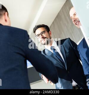 Un grupo de personas de negocios confiadas saludan con un apretón de manos en una reunión de negocios en una oficina moderna o cerrando el acuerdo de trato agitando las manos.