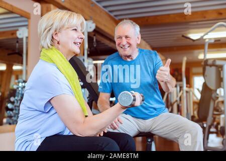 Mujer mayor en el gimnasio haciendo ejercicio con pesas para hacer ejercicio