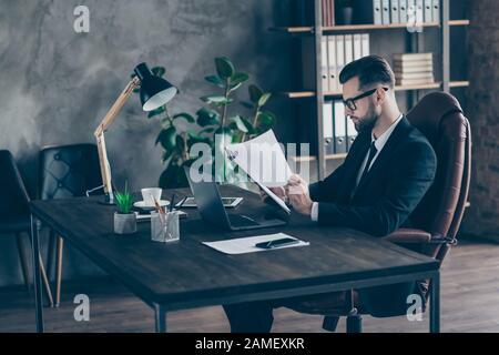 Foto de perfil de guapo negocio morena chico lectura informe de papel ingresos estadísticas cifras en busca de errores desgaste especificaciones negro blazer camisa traje