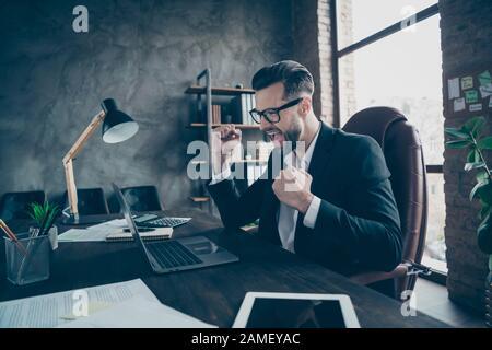 Foto de perfil de guapo hombre de negocios agarrando manos puños criados celebrando el éxito de nuevo proyecto de la compañía desgaste especificaciones negro blazer camisa traje