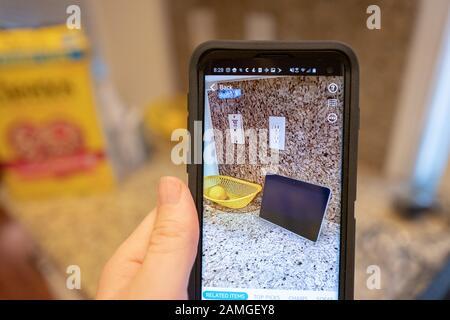 Mano de un hombre que sostiene un teléfono inteligente y que utiliza las funciones De Realidad aumentada en la aplicación de compras de Amazon para visualizar un dispositivo de Amazon Echo Show en una encimera de cocina, San Ramón, California, 22 de noviembre de 2019. AR se utiliza cada vez más como una característica para que los consumidores visualicen los productos en sus hogares antes de tomar una decisión de compra. ()