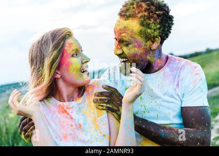 feliz hombre afroamericano tocando los hombros de la joven sorprendida con pinturas holi en la cara