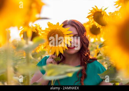 Retrato de una hermosa joven asiática con pelo rizado rojo y un vestido verde posando en un campo de girasoles en verano en un día soleado. Libertad
