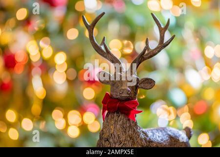 Primer plano de una decoración navideña en forma de ciervo de madera con luces de hadas defocused en el fondo