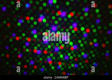 Telón de fondo desenfocado punto abstracto, arco iris de colores rojo verde violeta purpurina redonda sobre fondo negro. Iluminación luces borrosa, resumen