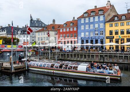 Dinamarca, Copehagen, Nyhavn, New Harbor waterfront revestidos con colores brillantes, bares, cafés y restaurantes & Canal Tours Boat