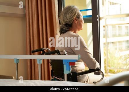 vista trasera de la mujer asiática mayor sentada en silla de ruedas en casa o en la sala del hospital mirando fuera de la ventana Foto de stock