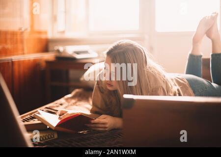 Mujer joven leyendo libro mientras se acostaba en la cama en casa Foto de stock