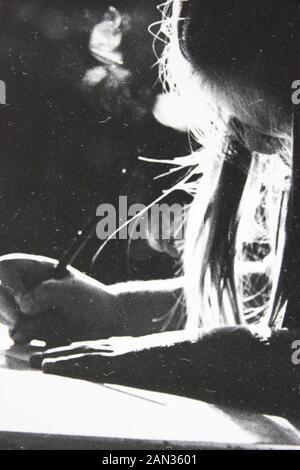Fotografía extrema blanca y negra de los años setenta de niña escribiendo en un escritorio con retroiluminación