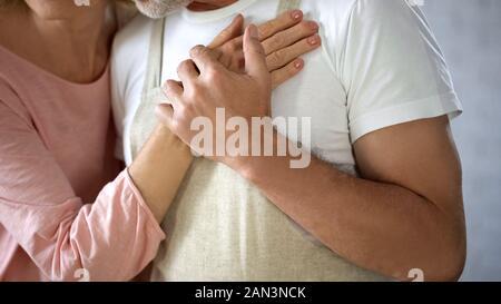 Jubilado hombre sujetando la mano de su esposa, la relación amorosa, momentos románticos, abuelos