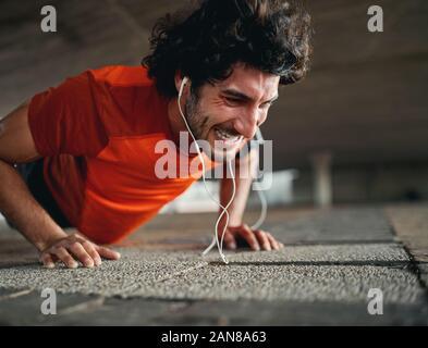Colocar joven hombre deportivo con expresión de cara seria haciendo difícil difícil gimnasia de tablones o empuje ups sobre pavimento Foto de stock