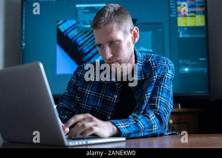 El fotógrafo masculinos sentados en la mesa trabajando en equipo, mediante la aplicación de software